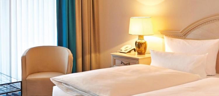 Aalernhüs Doppelzimmer Landblick – Bett mit Nachtschrank und Sessel